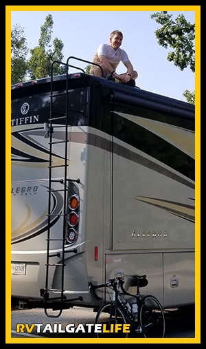 Dan on top of the RV with his bicycle at the bottom