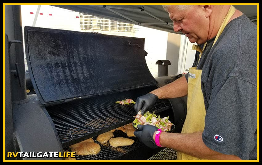 A tailgater adding things to the smoker grill during the tailgate. Use the Weber iGrill smartphone app to keep track of what is on the grill